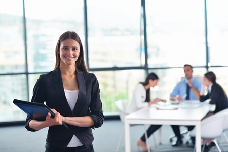 happy young business woman  with her staff,  people group in background at modern bright office indoors photo