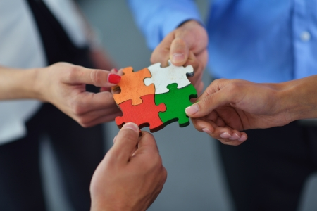 business puzzle: Group of business people assembling jigsaw puzzle and represent team support and help concept