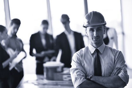 business people group on meeting and presentation  in bright modern office with construction engineer architect and worker looking building model and blueprint planbleprint plans Stock Photo - 22107221