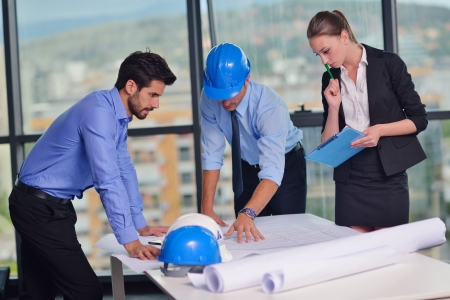 building blueprint: business people group on meeting and presentation  in bright modern office with construction engineer architect and worker looking building model and blueprint planbleprint plans Stock Photo