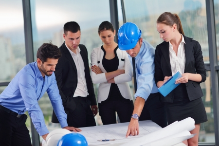executive helmet: business people group on meeting and presentation  in bright modern office with construction engineer architect and worker looking building model and blueprint planbleprint plans Stock Photo