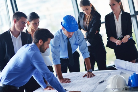 blue helmet: business people group on meeting and presentation  in bright modern office with construction engineer