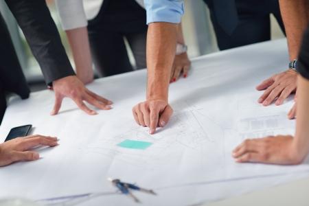 건설 엔지니어 건축가 및 작업자 찾고 건물 모델 및 청사진 planbleprint 계획과 만나 밝은 현대 사무실에서 프리젠 테이션에 사업 사람들의 그룹