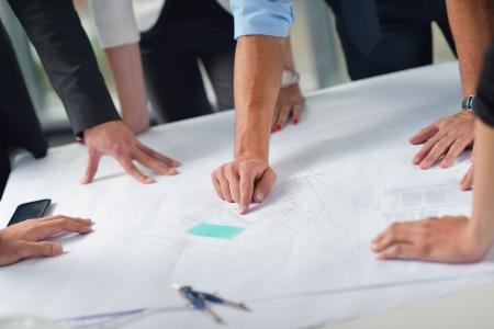 architect plans: business people group on meeting and presentation  in bright modern office with construction engineer architect and worker looking building model and blueprint planbleprint plans Stock Photo