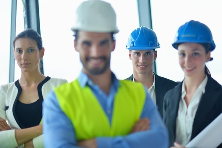 business people group on meeting and presentation  in bright modern office with construction engineer architect and worker looking building model and blueprint planbleprint plans Stock Photo - 22186080