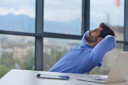 relaxando: trabalho homem de negócio nova feliz no escritório moderno no computador