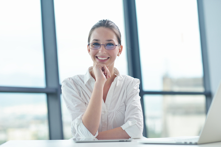 portrait of Young pretty business woman work on  notebook computer  in the bright modern office indoors Stock Photo - 22186099