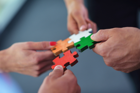 puzzle jigsaw: Group of business people assembling jigsaw puzzle and represent team support and help concept