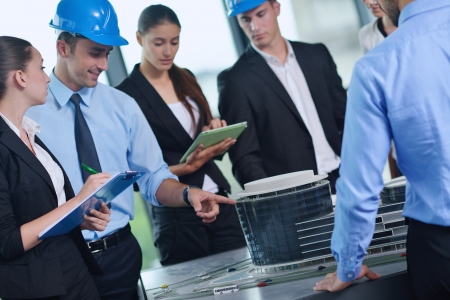 business people group on meeting and presentation  in bright modern office with construction engineer architect and worker looking building model and blueprint planbleprint plans Stock Photo - 22475556