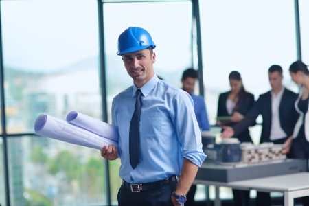 female architect: business people group on meeting and presentation  in bright modern office with construction engineer architect and worker looking building model and blueprint planbleprint plans Stock Photo
