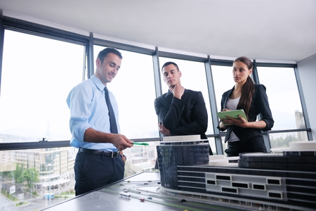 building plans: business people group on meeting and presentation  in bright modern office with construction engineer architect and worker looking building model and blueprint planbleprint plans Stock Photo
