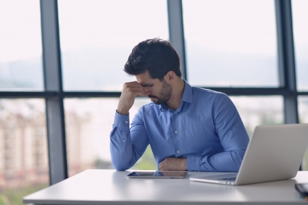 male headache: Young business man with problems and stress in the office Stock Photo