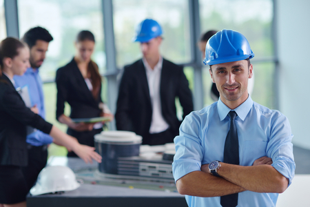 company building: business people group on meeting and presentation  in bright modern office with construction engineer architect and worker looking building model and blueprint planbleprint plans Stock Photo