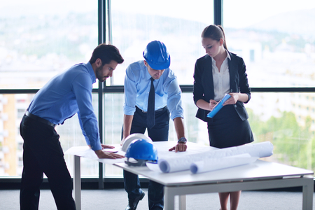 business people group on meeting and presentation  in bright modern office with construction engineer architect and worker looking building model and blueprint planbleprint plans Stock Photo - 22306452