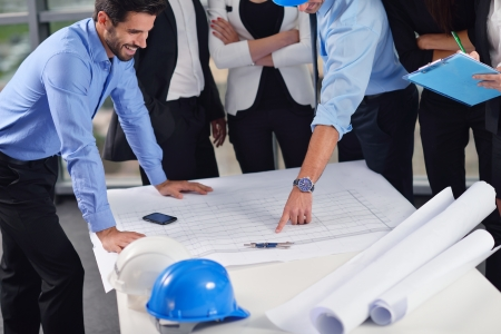 business people group on meeting and presentation  in bright modern office with construction engineer architect and worker looking building model and blueprint planbleprint plans Stock Photo - 22306453
