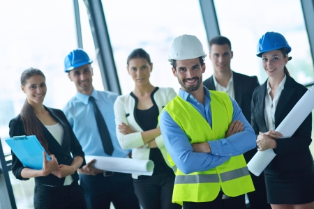 business people group on meeting and presentation  in bright modern office with construction engineer architect and worker looking building model and blueprint planbleprint plans Stock Photo - 22295533