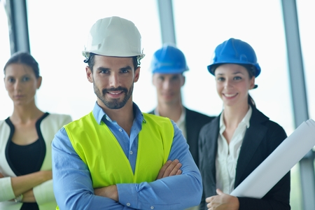 business people group on meeting and presentation  in bright modern office with construction engineer architect and worker looking building model and blueprint planbleprint plans Stock Photo - 22295530