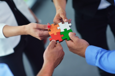 support team: Group of business people assembling jigsaw puzzle and represent team support and help concept