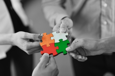 ジグソー パズルと代表チームのサポートおよびヘルプの概念を組み立てるビジネス人々 のグループ
