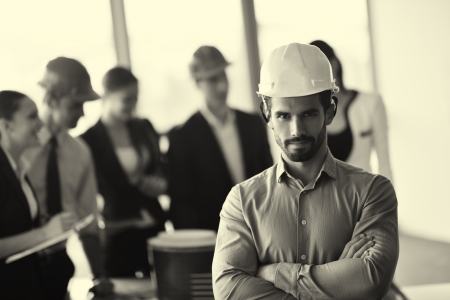 arab people: business people group on meeting and presentation  in bright modern office with construction engineer architect and worker looking building model and blueprint planbleprint plans Stock Photo