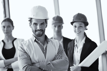 business people group on meeting and presentation  in bright modern office with construction engineer architect and worker looking building model and blueprint planbleprint plans Stock Photo