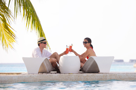 beach kiss: happy young couple relax and take fresh drink at summer vacation on swimmin pool