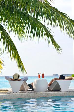 gelukkig jong koppel ontspannen en fris drankje in de zomer vakantie op swimmin zwembad