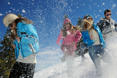 winter day: happy young people group have fun and enjoy fresh snow at beautiful winter day