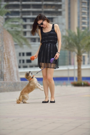 mujer con perro: hermosa mujer joven feliz en el vestido negro con lindo cachorro pequeño perro se divierte en la calle Foto de archivo