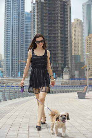 small dog: beautiful happy young  woman in black dress with cute small dog puppy have fun on street Stock Photo
