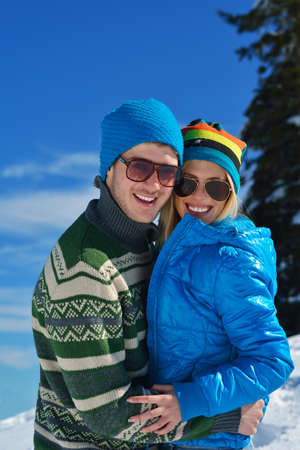 Young Couple In winter Snow Scene at  beautiful sunny day photo