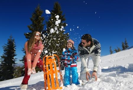 Winter season. Happy family having fun on fresh snow on vacation. Stock Photo