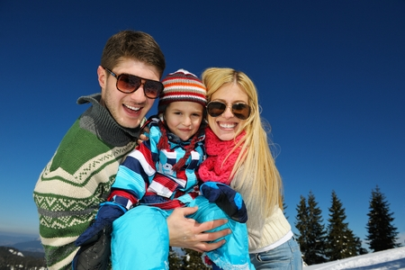 family vacation: Winter season. Happy family having fun on fresh snow on vacation. Stock Photo