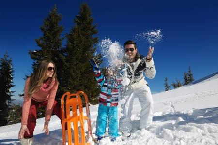ropa invierno: Temporada de invierno. Familia feliz que se divierte en la nieve fresca de vacaciones.