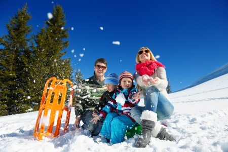 Winter season. Happy family having fun on fresh snow on vacation. Archivio Fotografico