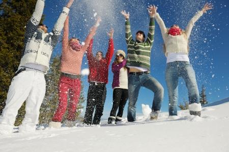 winter party: felice gruppo di giovani divertirsi e godersi la neve fresca in bella giornata invernale Archivio Fotografico