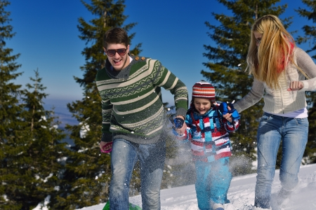 Winter season. Happy family having fun on fresh snow on vacation. photo