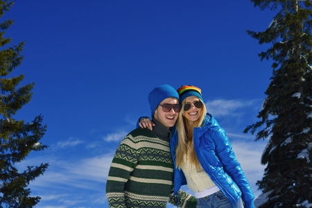Happy young couple has fun on fresh snow at beautiful winter sunny day on vacation photo