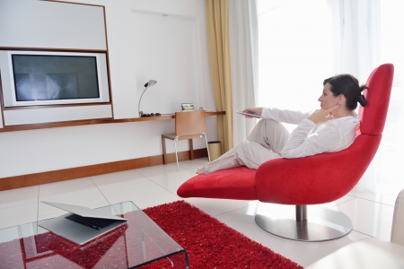 happy young woman relax at home on sofa in bright living room and watching tv photo