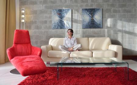 ver tv: Mujer joven feliz relajarse en casa en el sofá en la luminosa sala de estar y ver la televisión