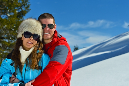 Happy young couple has fun on fresh snow at beautiful winter sunny day on relaxing vacation photo