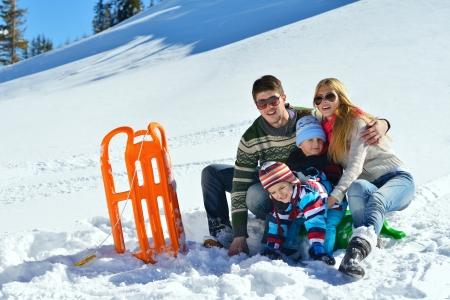 Winter season. Happy family having fun on fresh snow on vacation. photo