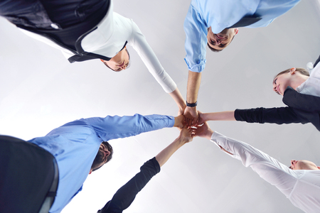 people isolated: business people group joining hands and representing concept of friendship and teamwork,  low angle view