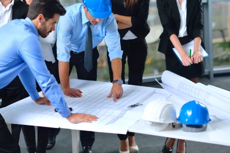 blue helmet: business people group on meeting and presentation  in bright modern office with construction engineer architect and worker looking building model and blueprint planbleprint plans Stock Photo
