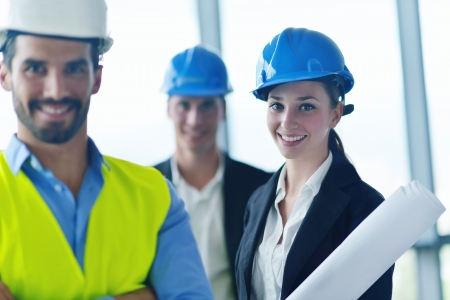 project manager: business people group on meeting and presentation  in bright modern office with construction engineer architect and worker looking building model and blueprint planbleprint plans Stock Photo