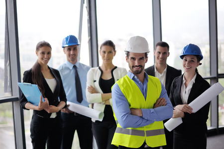 team success: business people group on meeting and presentation  in bright modern office with construction engineer architect and worker looking building model and blueprint  plans