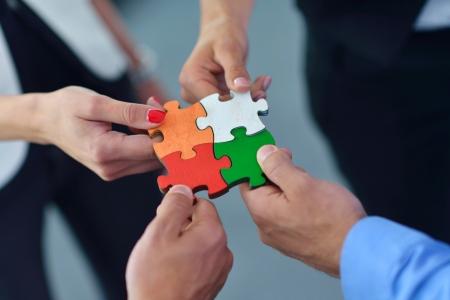 사업 사람들의 그룹이 지그 소 퍼즐을 조립 및 팀 지원과 도움 개념을 나타내는