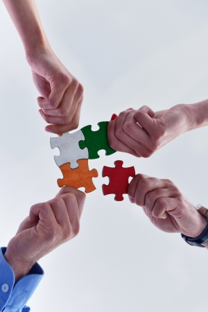 creative concept: Group of business people assembling jigsaw puzzle and represent team support and help concept