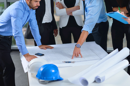 female architect: business people group on meeting and presentation  in bright modern office with construction engineer architect and worker looking building model and blueprint  plans