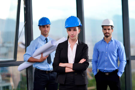 woman engineer: business people group on meeting and presentation  in bright modern office with construction engineer architect and worker looking building model and blueprint  plans